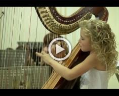 Esta niña de 9 años se sienta con una arpa. La música que produce es celestial