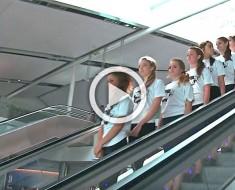 Ocho chicas forman una línea recta. Cuando se bajen de la escalera mecánica mira sus pies